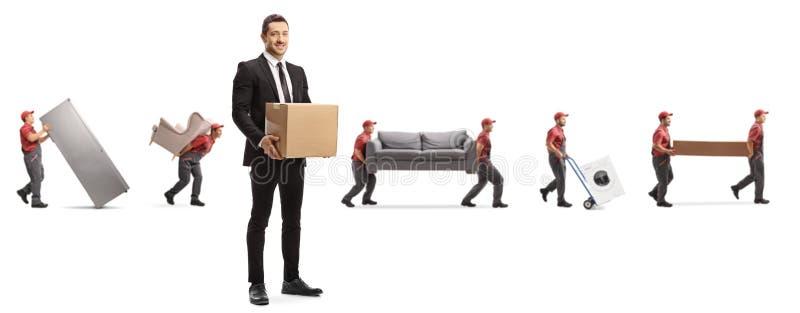 Мужчина в костюме с картонной коробкой и рабочие из движущейся компании, несущие домашние яблоки и мебель стоковые фото