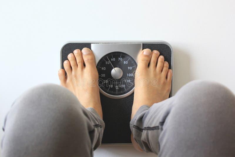 Мужчина в масштабе веса для контрольной массы, концепции диеты стоковая фотография