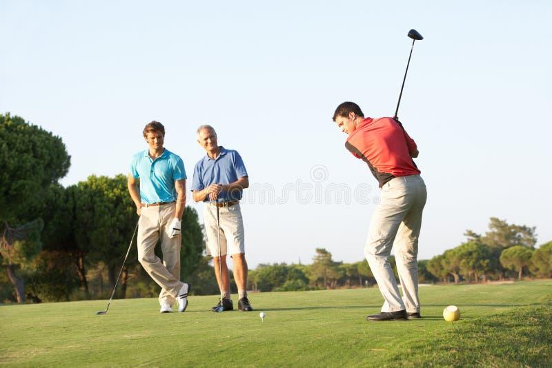 мужчина группы игроков в гольф с teeing стоковые изображения rf