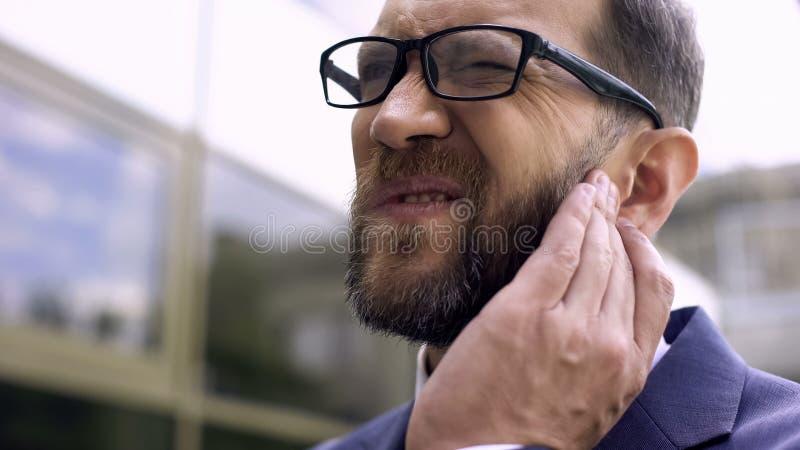 Мужчина дела имеет боль уха, бактериальную инфекцию, воспаление, заболевание otitis стоковое изображение
