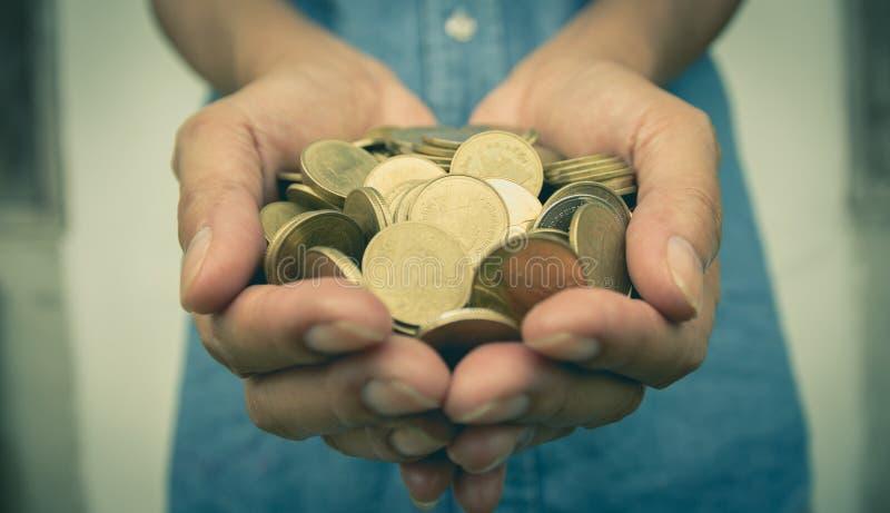 Мужчина держа золотые монетки денег в ее руке для финансового стоковое изображение rf