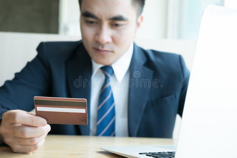 Мужчина держа кредитную карточку и используя портативный компьютер для онлайн стоковые фото