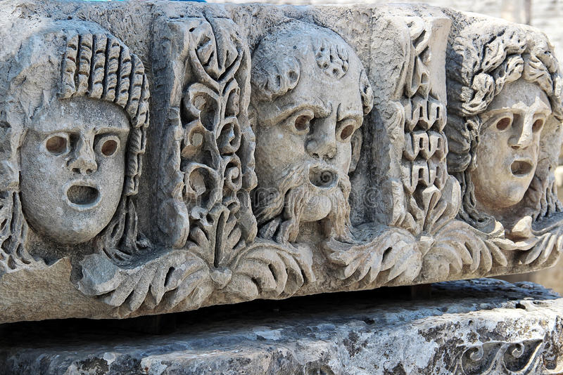 Мужчина и женская театральная маска высекли на каменной поверхности стоковые фото