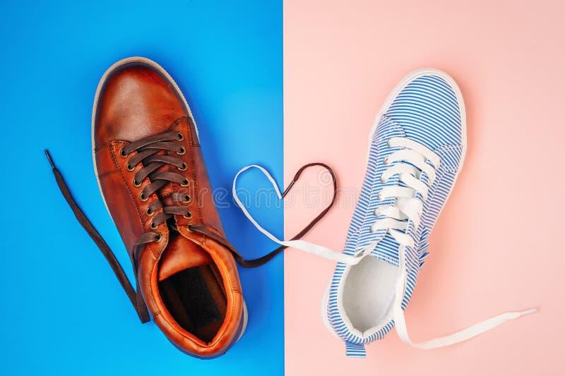 Мужчина и женские ботинки на голубой и розовой предпосылке со шнурками в форме сердца, взгляда сверху стоковые фото
