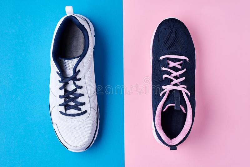 Мужчина и женские ботинки спорта на пастельной сини и розовой предпосылке, взгляде сверху Минимальный стиль моды стоковая фотография rf