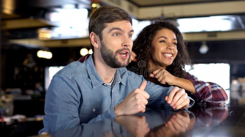 Мужчина и женские вентиляторы празднуя победу команды, наблюдая конкуренцию спорта онлайн стоковые фото