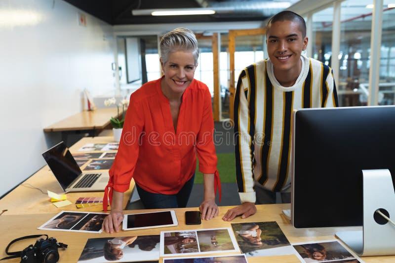 Мужчина и женские график-дизайнеры стоя совместно на столе в офисе стоковые изображения rf