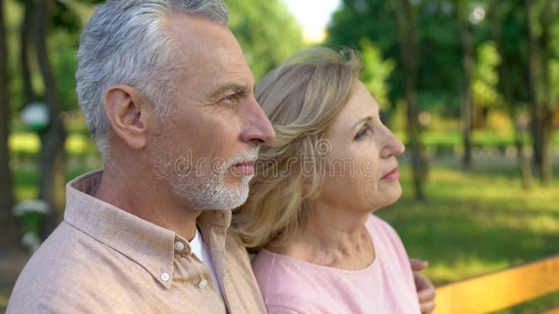 Мужчина и женские пенсионеры наблюдая парк захода солнца совместно, наслаждаясь взглядом природы стоковые изображения rf