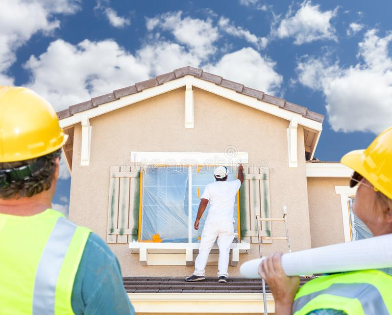 Мужчина и женские подрядчики обозревая дом картины художника стоковая фотография