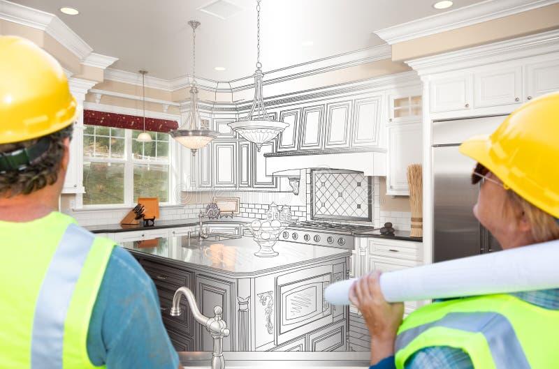 Мужчина и женские подрядчики обозревая переход чертежа кухни к завершенному проекту стоковые изображения rf