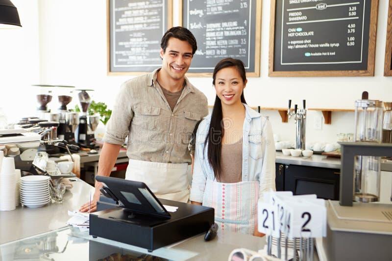 Мужчина и женский персонал в кофейне стоковое фото