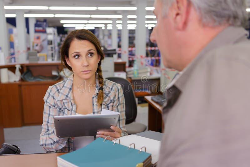 Мужчина и женщина используя таблетку на офисе стоковое фото rf