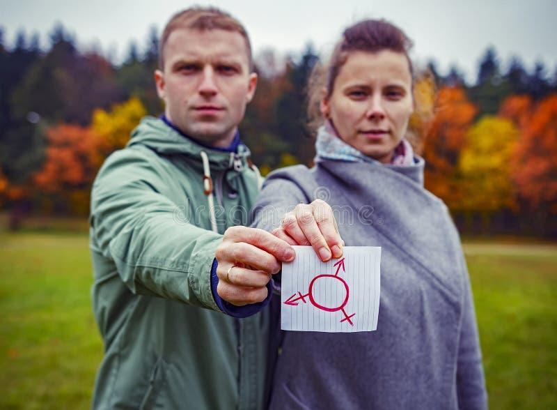 Мужчина и женщина совместно держа бумагу части с символом трансгендерного чертежа Человеческие права секса Символ рода стоковая фотография rf
