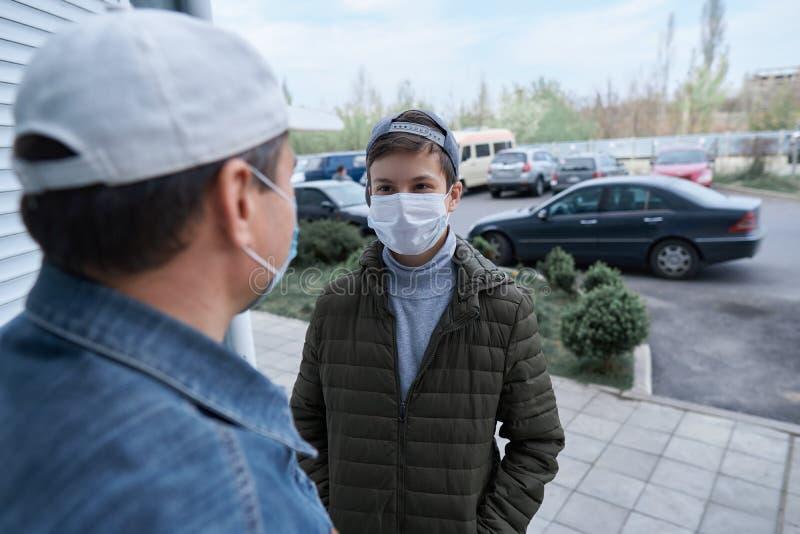 Мужчина и подросток позируют у стены и закрывают двери высотных зданий с квартирами, жилой зоной, медицинской маской на стоковая фотография