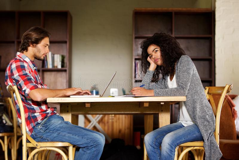 Мужчина и студентки сидя дома изучать стоковая фотография