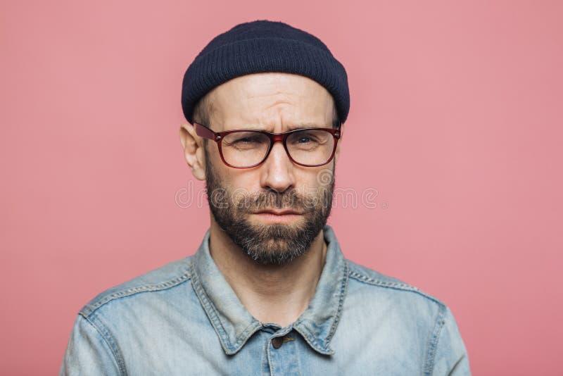 Мужчина несчастного недовольства небритый смотрит с сварливым выражением в камеру, носит черную шляпу стекел и стильную рубашку д стоковые изображения