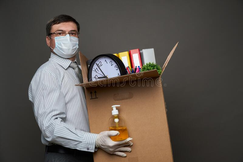 Мужчина, одетый как бизнесмен, держит коробку с офисными вещами, документами, ручным санитизатором, позируя в студии на сером фон стоковое фото rf