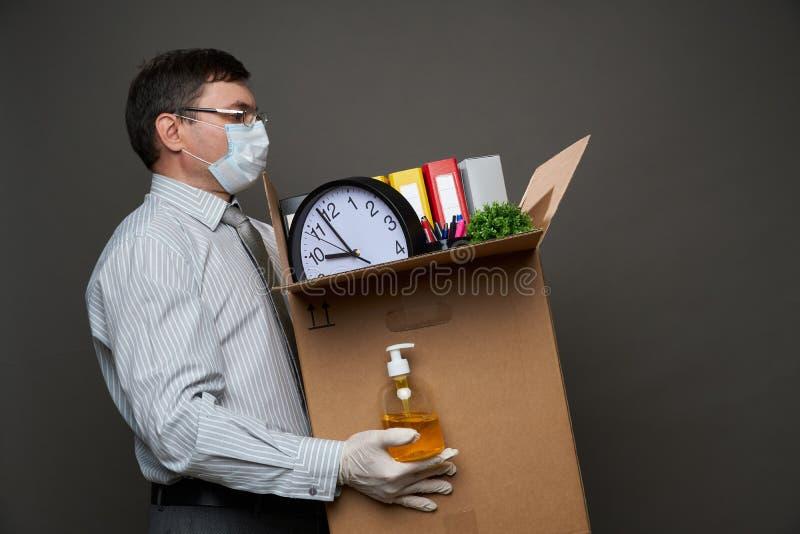 Мужчина, одетый как бизнесмен, держит коробку с офисными вещами, документами, ручным санитизатором, позируя в студии на сером фон стоковое изображение
