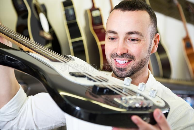 Мужчина покупая новую гитару стоковые изображения rf