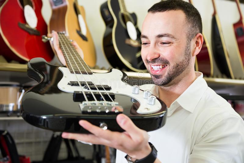 Мужчина покупая новую гитару стоковые фотографии rf
