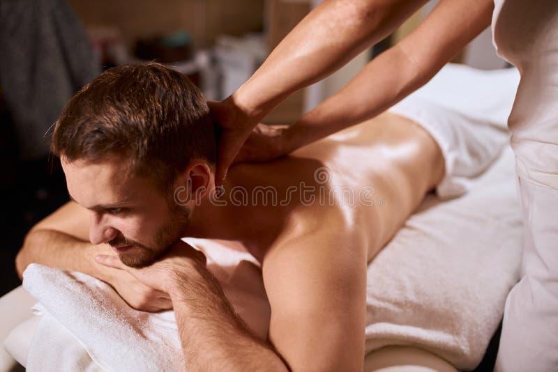 Мужчина, получающий массаж в спине от массажиста в спа-салоне стоковые фотографии rf