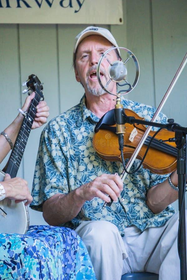 Мужчина поя и играя скрипку стоковая фотография