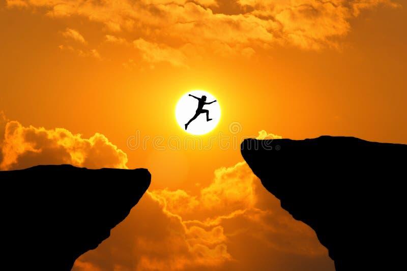 Мужчина прыгает сквозь пропасть между холмом человек, прыгающий по обрыву стоковые фотографии rf