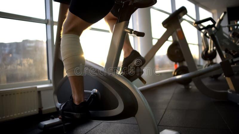 Мужчина спортсмена при перевязанная нога ехать неподвижный велосипед в утре, спасении стоковая фотография rf