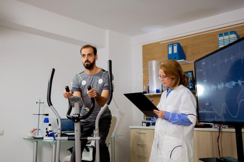 Мужчина-спортсмен, который делает физическое усилие на ступеньке и имеет к ней электроды, и врач делает заметки на стоковое фото rf