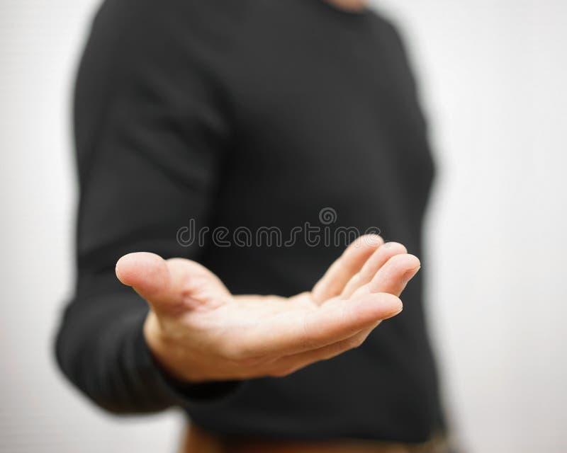 Мужчина стоит и показывает протягиванная рука с открытой ладонью стоковая фотография rf