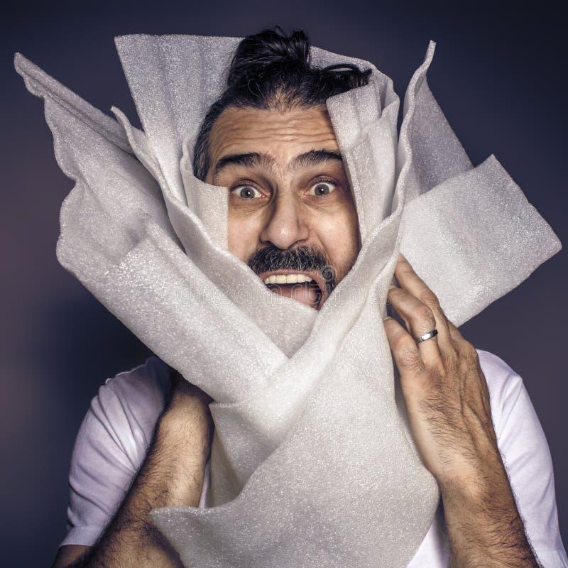 Мужчина с длинными волосами и бородатыми криками, завернутыми в пластиковую упаковку стоковая фотография rf