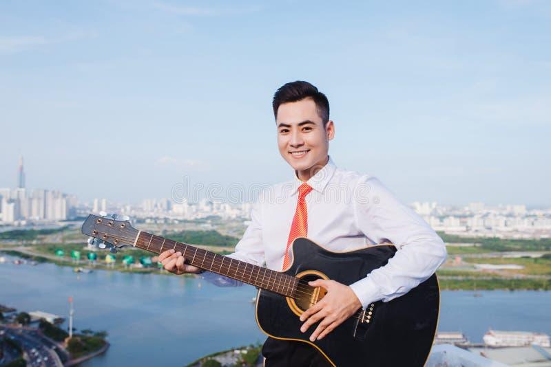 Музыкальная принципиальная схема Вскользь человек играя практикуя гитару стоковая фотография