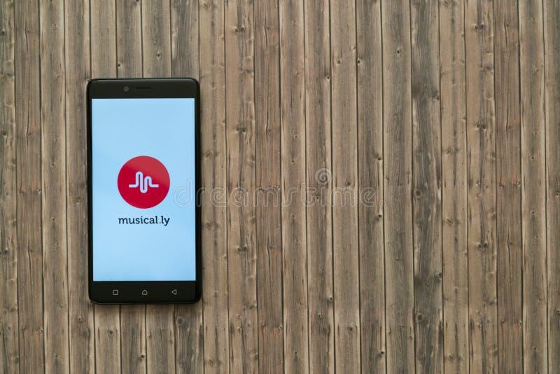 музыкально логотип ly на экране smartphone на деревянной предпосылке стоковые изображения