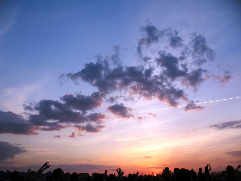Музыкальный спектакль, который дали публично Красивое небо захода солнца над толпой людей стоковая фотография