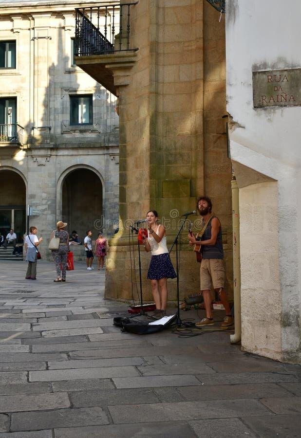 Музыканты улицы выполняя перед собором Квадрат с туристами, Santiago de Compostela Platerias, Испания стоковое изображение