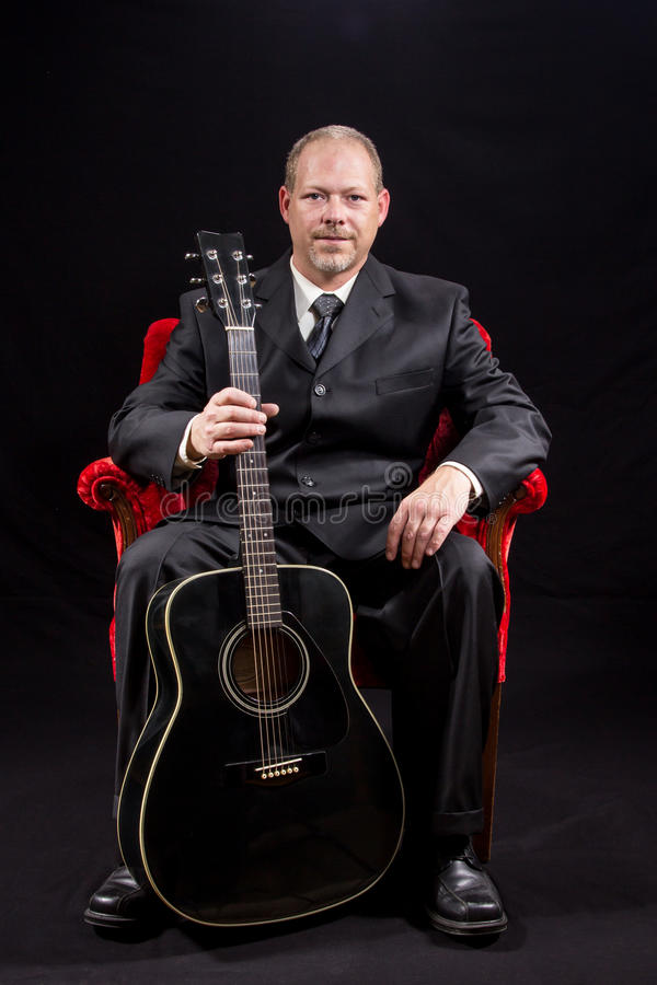 Музыкант в деловом костюме сидя в красном стуле бархата держа гитару стоковые фотографии rf