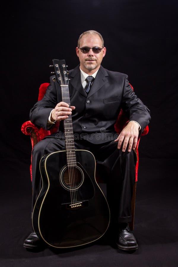 Музыкант в деловом костюме сидя в красном стуле бархата держа гитару стоковые изображения