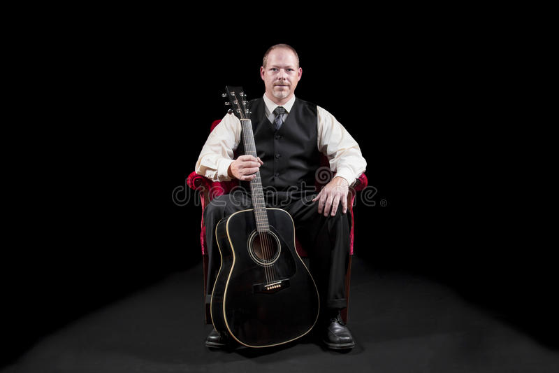 Музыкант в жилете и связь сидя в красном бархате предводительствуют держать гитару стоковое изображение