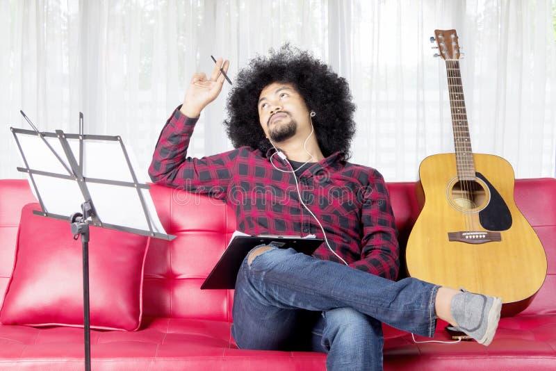Музыкант думает для составлять песню дома стоковая фотография