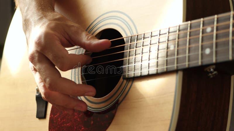 Музыкант играет на желтой акустической гитаре, близко к гитарной палубе акции видеоматериалы