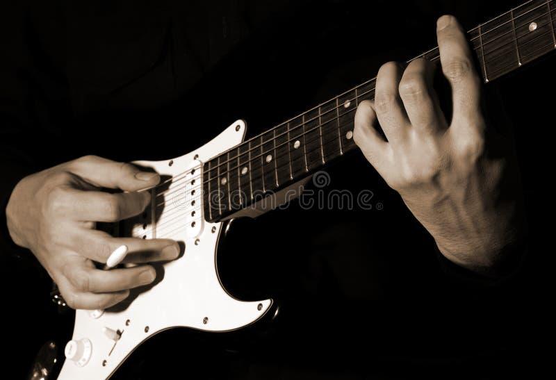 Музыкант играя гитару стоковое изображение