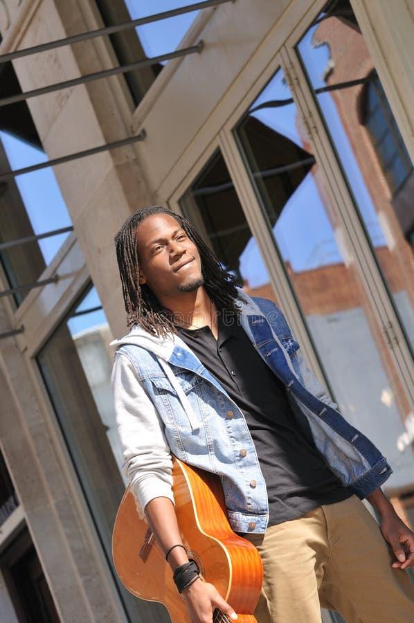 Музыкант идя в улицу с гитарой стоковые фотографии rf