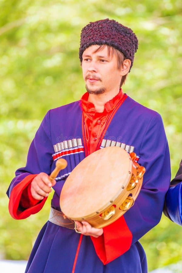 Музыкант казака держит тамбурин в его руках и бьет его с загонщиком стоковые фотографии rf