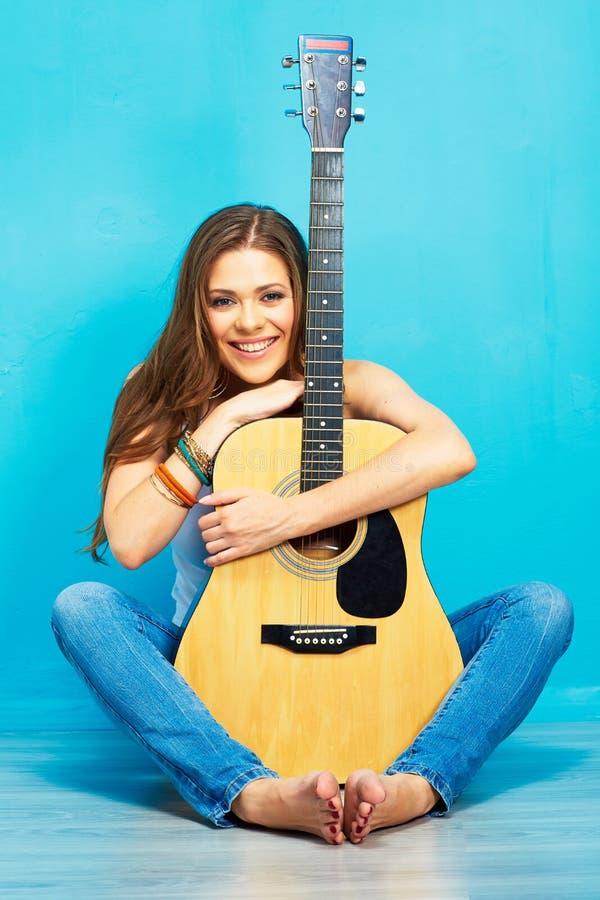 Музыкант молодой женщины при гитара сидя на поле стоковая фотография rf