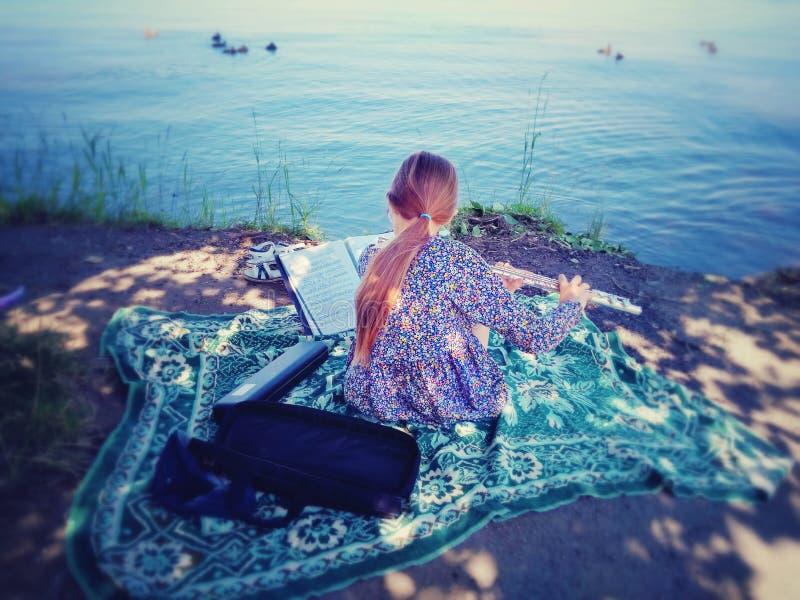 Музыкант на реке стоковое изображение