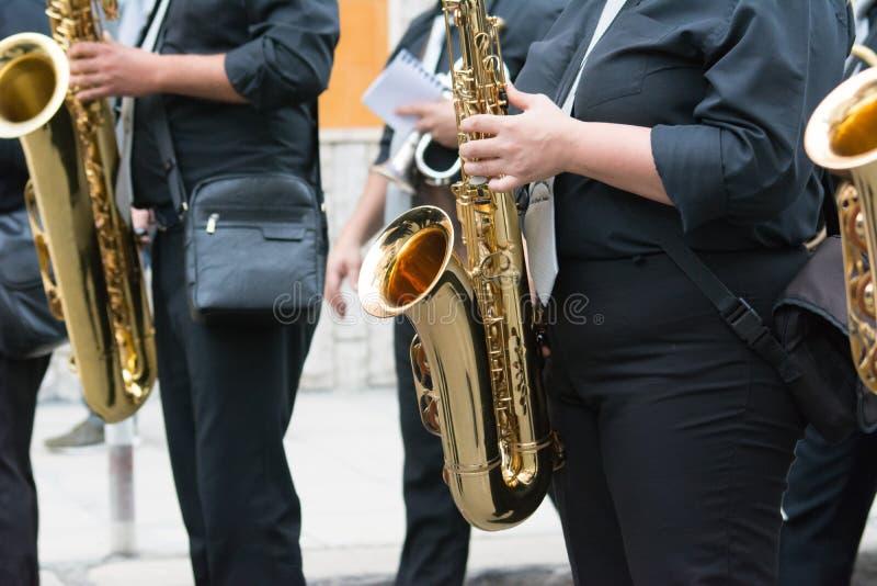 музыкант саксофона идя в улицу стоковое изображение rf