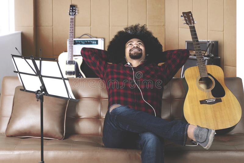 Музыкант слушает к музыке находя воодушевленность для записи песни стоковая фотография rf