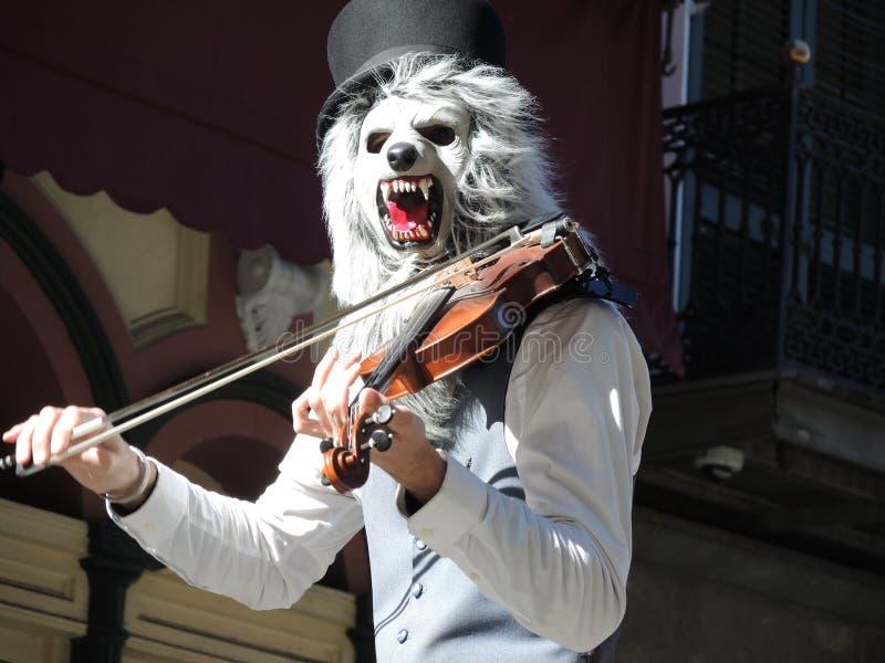 Музыкант с маской играя скрипку стоковое фото rf