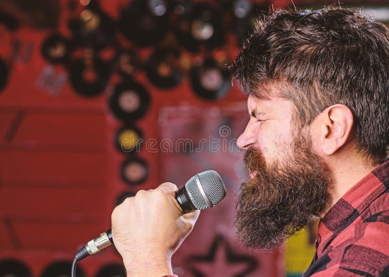 Музыкант с песней петь бороды и усика в караоке Концепция панковского утеса Человек с напряженной стороной держит микрофон стоковое фото rf