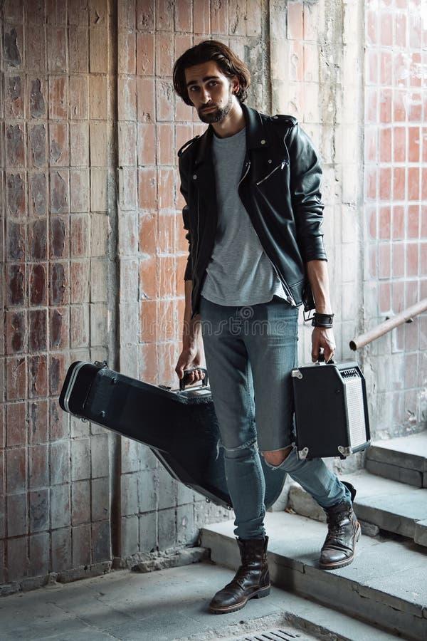 Музыкант улицы держа случай с гитарой и усилителем Пошл вниз к подземному переходу r Игра для того чтобы заработать деньги a стоковые фотографии rf